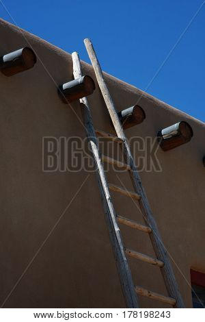 A wooden ladder is leaning against the wall of an adobe structure between two vigas in New Mexico
