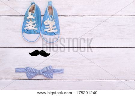 The accessories of a little gentleman lie on a white wooden background. View from above