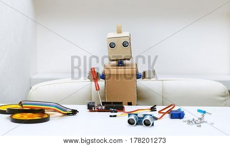 The robot holds a screwdriver next are the parts for assembling the robot