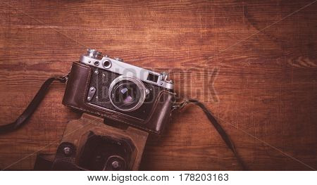 Retro camera on wood table background vintage color tone