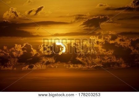 Layers of clouds partially mask rising sun