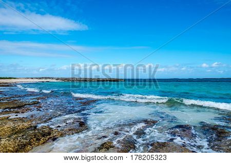 A beautiful tropical cove with rocks, clouds, and waves. New Providence Island, Nassau, Bahamas.
