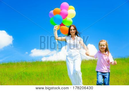 mother and daughter running on green meadow, holding colorful balloons