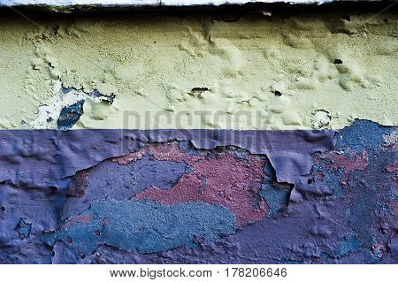 Rotten concrete old wall with blown paint .