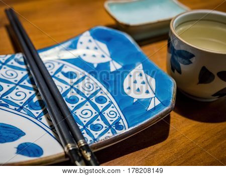 Japanese style ceramic tableware, together with chopsticks and a cup of green tea. Image captured under indoors condition.