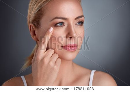 nourished middle age woman looking at wrinkles around the eyes