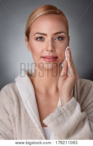 portrait of smiling woman cleaning face with cotton pad