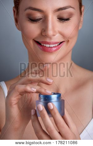 Smiling woman holding cosmetic cream in hand