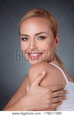 Gorgeous woman hugging herself and laughing happily, she love her skin
