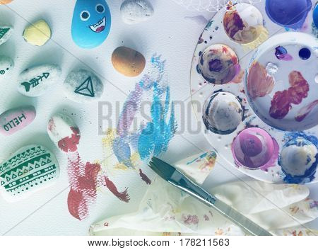 Painting palette pebbles brushes white table