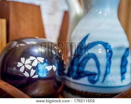 Japanese style ceramic tableware, featuring a condiment shaker with sakura (cherry blossom) motif. Image captured under indoors condition.