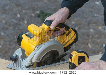 Hand Operating Circular Saw Cutting Wood with Tape Measure