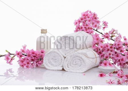 Branch pink cherry on three rolled towel ,salt in bowl ,oil isolated