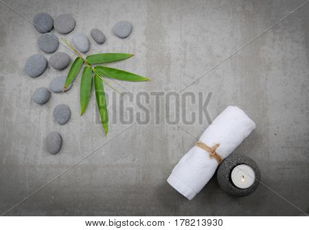 Gray stones with bamboo leaf,towel, candle -gray background