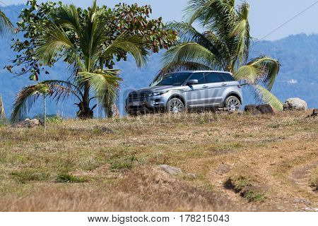 Puntarenas Costa Rica - February 25: Range Rover Evoke parked under palm trees in a dry rocky cliff in Costa Rica. Puntarenas Costa Rica - February 25