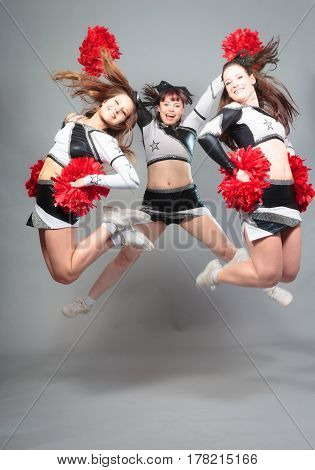 Studio shot of two cheerleaders jumping in front of grey background