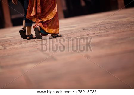 two ladies walking on a sanstone floor at fatehpur sikri