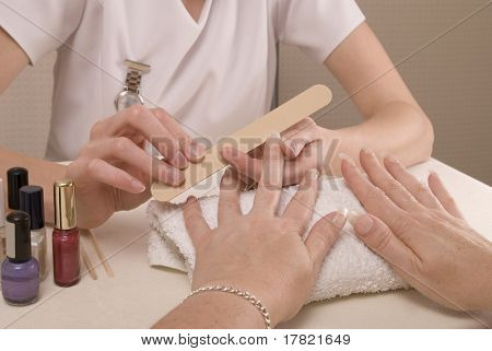 Woman having a manicure by a professional nail technician