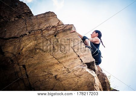 Young climber rock climbing in old quarry