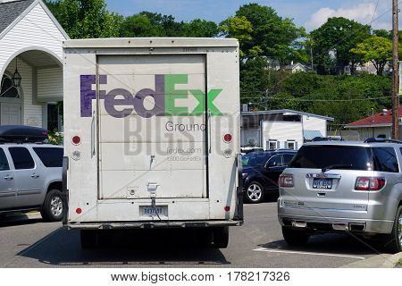 HARBOR SPRINGS, MICHIGAN / UNITED STATES - AUGUST 4, 2016: A Federal Express truck delivers packages in downtown Harbor Springs.