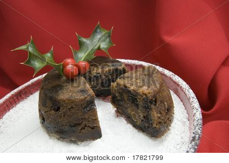 Slice and  Christmas pudding with holly & berry sprig on glass dish dusted with icing sugar