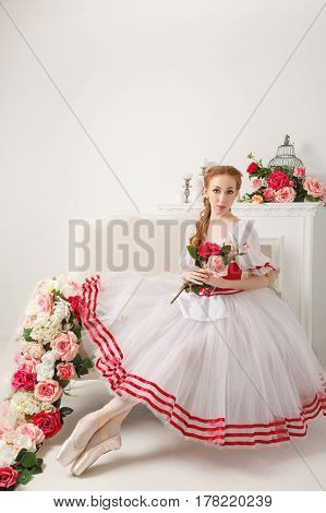 Cute ballerina in stage costume holding a bouquet of spring flowers. Retro dress.