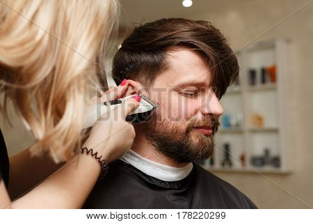 Professional hairdresser doing haircut men's hair. Cutting electric razor. Beauty saloon. Male beauty. The client is a hipster.
