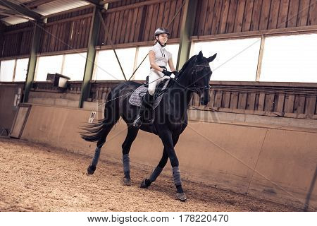 Young Girl Riding Her Horse in Indoor Riding Arena