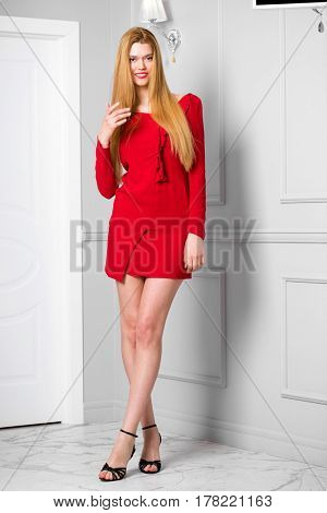 Fashion portrait of pretty sexy young blonde woman posing on gray wall background