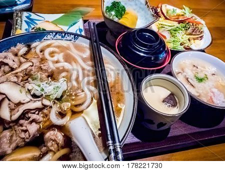 Japanese set meal, featuring a bowl of beef and mushroom udon noodle soup. Image captured under available light.