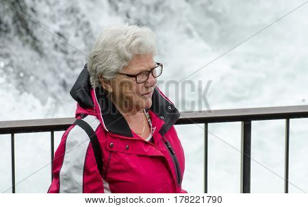 Elderly Tourist Woman At Rhine Falls, The Largest Plain Waterfall In Europe