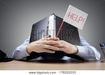 Frustrated and overworked businessman burying his head under a laptop computer asking for help
