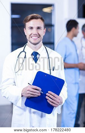Doctor holding medical report and smiling at camera while his colleagues discussing in background