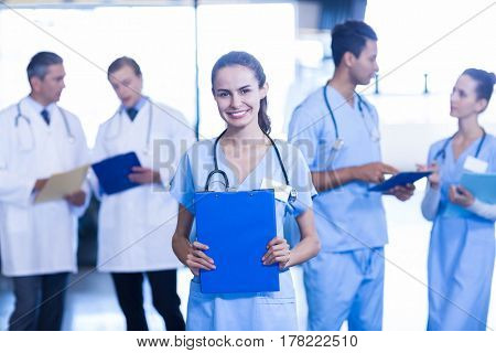 Female doctor holding medical report and smiling at camera while her colleagues discussing in background