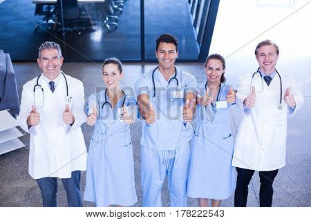 Portrait of medical team putting their thumbs up and smiling