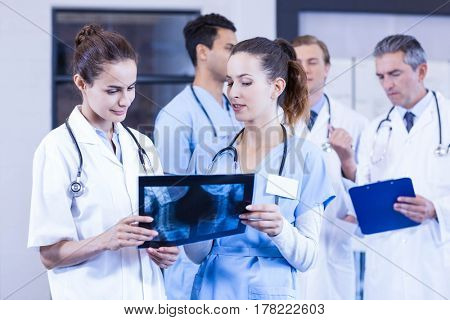 Female doctors checking x ray reports and male doctors discussing behind