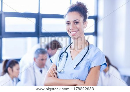 Portrait of female doctor smiling at camera and other doctors discussing behind in conference room