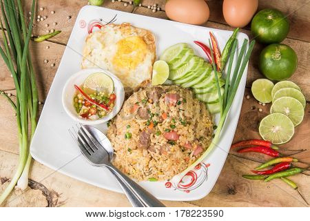 fried rice with vegetables, meat and fried eggs served on a plate with chopsticks