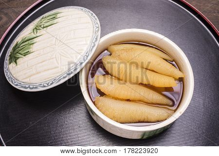 Several yellow Kazunoko(herring roe) into the soup stock on round depth plate with lid