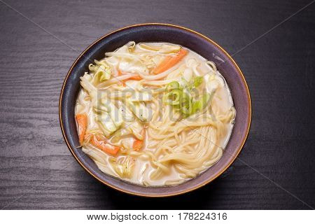 Chinese noodles with various slice vegetables in pottery bowl