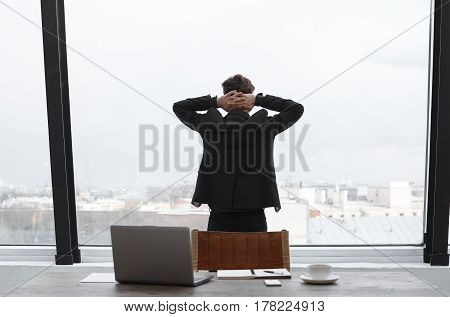 Man keep crossed hands behind head in office in time break and look to the city through the office window on top floor. Well dressed man back to the job with internet technology soon after meditation.
