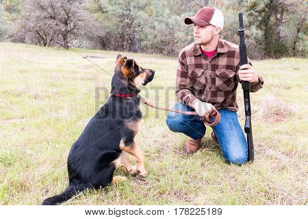 Young Man Hunting With German Shepherd Puppy