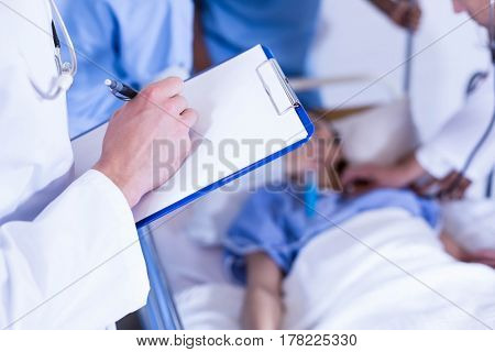 Doctor writing on clipboard and other doctor examining a patient behind in hospital