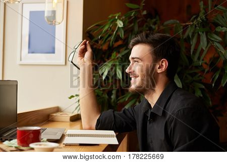 Side portrait of perfect look handsome caucasian man laughing and keep eye glasses in the hand. Guy get good news in the internet. Talented male editor start working morning in cafe.
