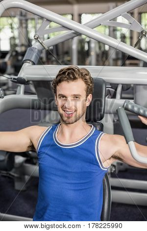 Fit man using weight machine at gym