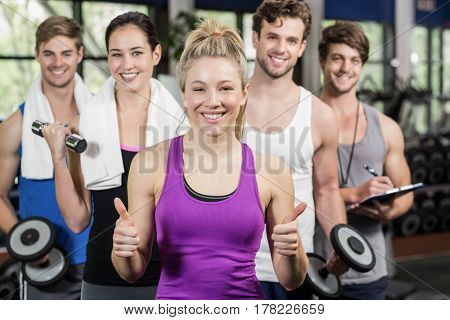 Fitness group lifting dumbbells and showing thumbs up in gym