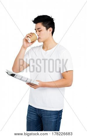 Young man having coffee and reading newspaper on white background