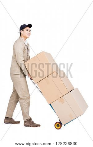Delivery man moving luggage trolley with cardboard boxes on white background