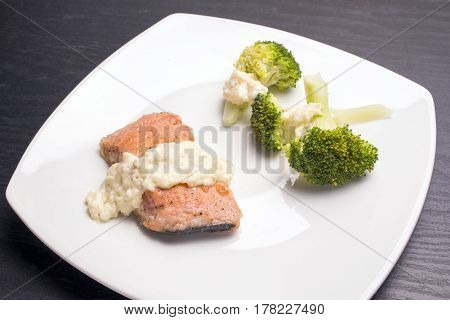 Close up meuniere salmon and vegetable with bechamel sauce on white plate