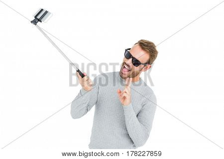 Young man taking a selfie with selfie stick on white background